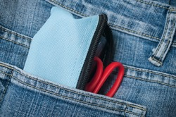 closeup of pencilcase and scissors on blue jeans pocket