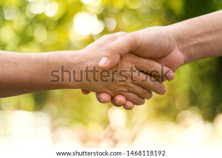 Closeup of people holding hands on a green bokeh background. #1468118192