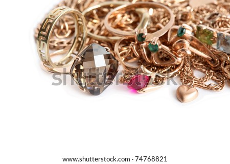 Closeup of pile of gold jewelry on white background