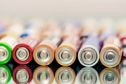 Closeup of pile of used alkaline batteries. Close up colorful rows of selection of AA batteries energy abstract background of colorful batteries. Alkaline battery aa size. Several batteries in rows.