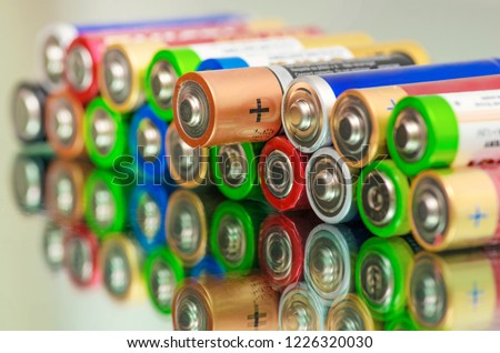 Photo of  Closeup of pile of used alkaline batteries. Close up colorful rows of selection of AA batteries energy abstract background of colorful batteries. Alkaline battery aa size. Several batteries in rows.