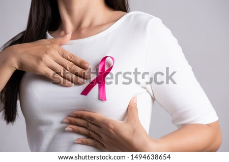 Closeup of pink badge ribbon on woman chest to support breast cancer cause. Healthcare, medicine and breast cancer awareness concept.
