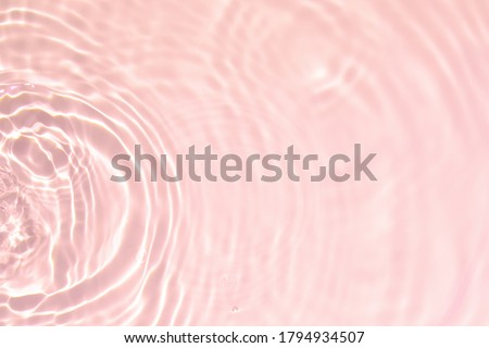 Photo of  Closeup of pink transparent clear calm water surface texture with splashes and bubbles. Trendy abstract summer nature background. Coral colored waves in sunlight.
