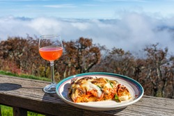 Closeup of pizza slice on plate on balcony terrace by red rose wine drink in garden outside in Blue Ridge mountains with fog foggy mist above view in Wintergreen