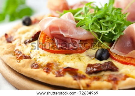 Closeup of pizza with prosciutto and arugula