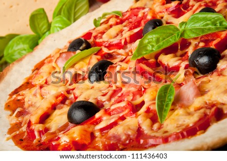 Closeup of pizza with tomatoes, cheese, black olives and peppers
