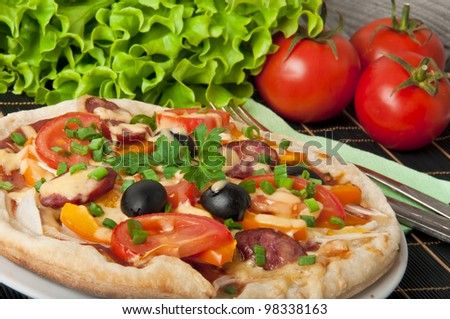 Closeup of pizza with tomatoes, cheese, black olives and peppers.