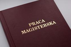 Closeup of Polish Master's Thesis (Praca magisterska) on white background.