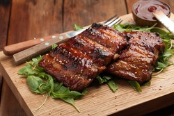 Closeup of pork ribs grilled with BBQ sauce and caramelized in honey on a bed of arugula. Tasty snack to beer on a wooden Board for submission on the old wooden background. Top view.