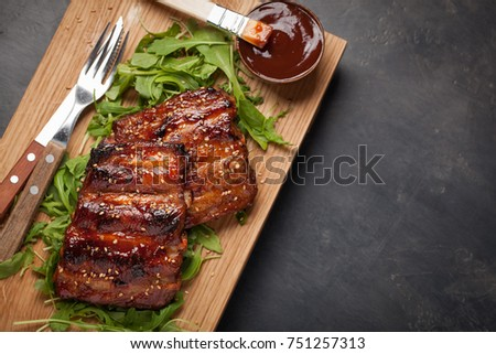 Stock Photo Closeup of pork ribs grilled with BBQ sauce and caramelized in honey on a bed of arugula. Tasty snack to beer on a wooden Board for filing on dark concrete background. Top view with copy space.