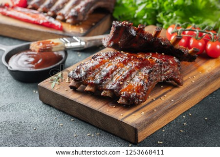 Closeup of pork ribs grilled with BBQ sauce and caramelized in honey. Tasty snack to beer on a wooden Board for filing on dark concrete background