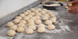 Closeup of portioned pieces of dough prepared for shaping and rolling on metal working surface with flour in bakery