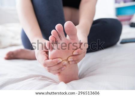 Closeup of pregnant woman hands doing foot massage