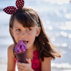 Closeup of pretty little girl eating ice cream outdoors on sunny day. Cute girl in pink swimsuit licking purple ice-cream in waffle cone. Summer, happy childhood concept. Copy space for your text