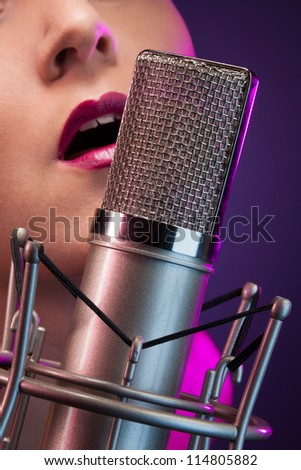 closeup of pretty woman singing in microphone on stage - stock photo
