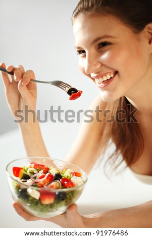 Closeup of pretty young woman eating vegetable salad