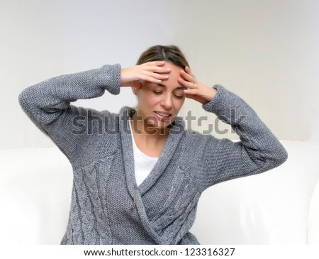 Closeup of pretty young woman suffering from head pain while sitting at home