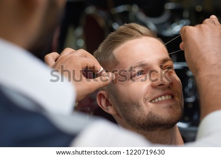 Closeup of process of threading procedure in barber shop. Professional barber correcting shape of brows with threads to smiling young man sitting in chair. Concept of eyebrows care.