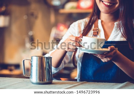 Closeup of professional female barista hand making and holding white cup of coffee. Happy young woman at counter bar in restaurant background. People lifestyles and Business occupation concept #1496723996