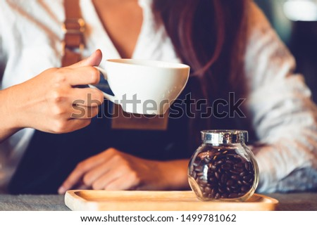 Closeup of professional female barista hand making and holding white cup of coffee. Happy young woman at counter bar in restaurant background. People lifestyles and Business occupation concept #1499781062