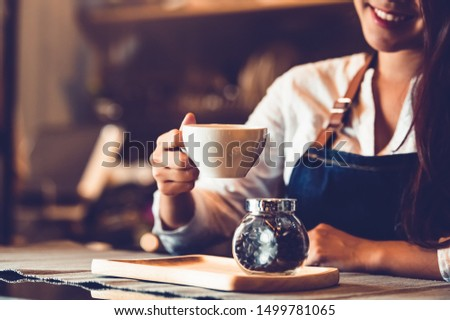 Closeup of professional female barista hand making and holding white cup of coffee. Happy young woman at counter bar in restaurant background. People lifestyles and Business occupation concept #1499781065