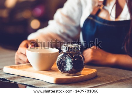 Closeup of professional female barista hand making and holding white cup of coffee. Happy young woman at counter bar in restaurant background. People lifestyles and Business occupation concept #1499781068