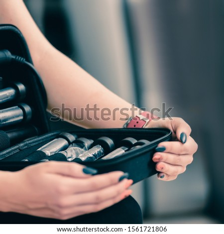 Closeup of professional hairdresser holding tools for hair styling