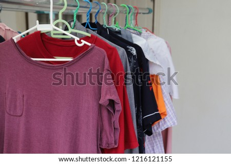 Closeup of purple T-shirt and others hanging on hangers drying under sunlight, The simply way of family life and enery saving.