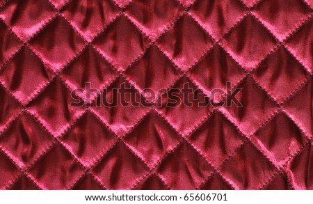 Closeup of quilted red satin fabric