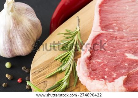 Closeup of raw New York strip steak on a wood.