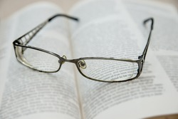 Closeup of reading glasses on the book