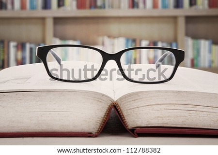 Closeup of reading glasses on the book. shot in the library