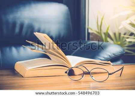 Closeup of reading glasses with open book on wood table