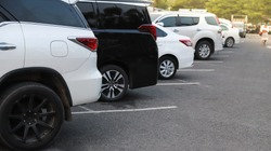 Closeup of rear, back side of white minii-van car with  other cars parking in outdoor parking area with natural background in bright sunny day.