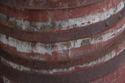 closeup of red and white painted traditional wood barrel with rusty iron hoops bands