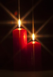 Closeup of red burning candle on dark black background