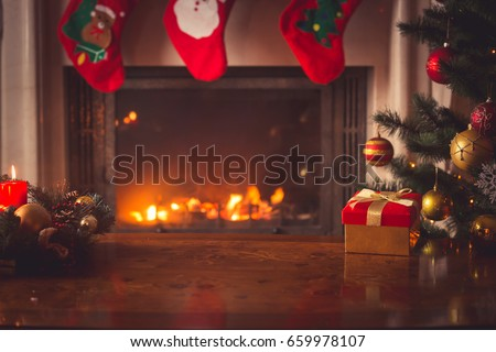 Closeup of red Christmas gift box with golden ribbon next to decorated Christmas tree and fireplace
