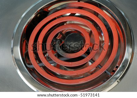 Closeup of red hot electric burner on kitchen stove.