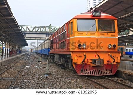 Closeup of Red orange train, Diesel locomotive, on Bangkok railway station platform Thailand