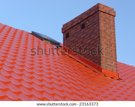 Closeup of red roof metal covering with brick-made chimney