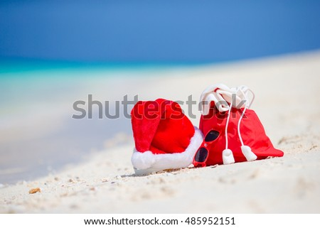 Closeup of red Santa bag and Santa Claus hat on beach. Xmas travel vacation and travel cuprise concept. Beach accessories with Santa Hat on white tropical beach #485952151
