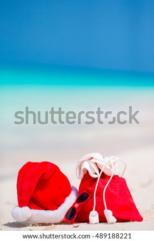 Closeup of red Santa bag and Santa Claus hat on beach. Xmas travel vacation and travel cuprise concept. Beach accessories with Santa Hat on white tropical beach #489188221