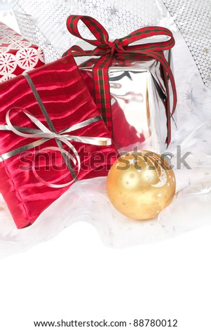Closeup of red, silver, and gold wrapped Christmas gifts with pretty ribbons and ornaments. Silver star translucent fabric backdrop on white. Vertical format with copy space.