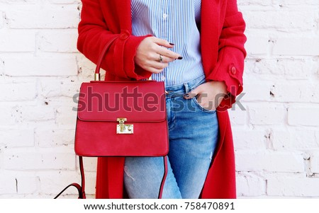 Closeup of red small bag in hand of woman. Fall spring fashion outfit red coat and trendy blue jeans