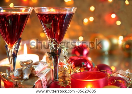 Closeup of red wine in glasses,candle lights, gift box,baubles and twinkle lights on background.