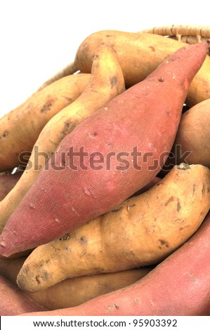 Closeup of red yams and sweet potatoes in basket - stock photo
