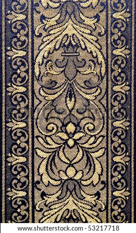 Closeup of retro tapestry fabric pattern with classical floral ornament  in light-yellow and dark-blue tones.
