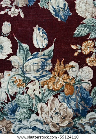 Closeup of retro tapestry fabric pattern with classical image of the colorful  floral ornament on dark cherry background.