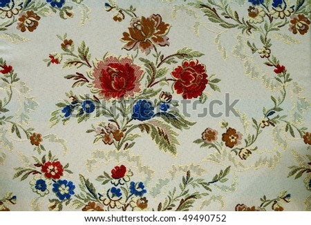 Closeup of retro tapestry fabric pattern with colorful  floral   lacy design.