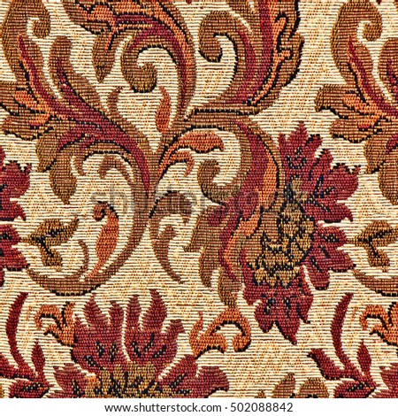 Closeup of retro tapestry fabric pattern with colorful floral ornament in classical style.
